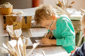 Child writing letter with quill pen